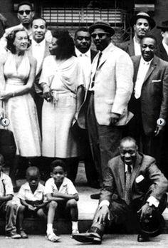 Harlem 1958 jazz portrait - Some of the entertainers were: L-R: Marian McPartland, sonny Rollins (back) Lawrence Brown, Mary Lou Williams, Emmett Berry, Thelonious monk, Count Basie (seated), Vic Dickenson, Milt Hinton - Basie grew tired of standing, sat down on the curb and a group of kids followed him.