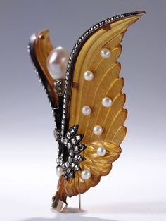 Winged comb head which was originally a tiara comb. Bleached tortoise-shell with gold and silver, set with rose-and brilliant-cut diamonds and pearls; the comb teeth are missing.  Place of Origin  France (probably, made)  Date  ca. 1900 (made)  Artist/maker  Unknown (production)  Materials and Techniques  Tortoise-shell, diamonds and pearls, gold, silver