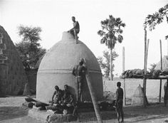 Africa |Chad | 1925 | Men recover millet attic |  Allégret Marc photograph
