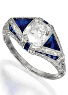 An Art Deco platinum, diamond and sapphire ring, circa 1920. Set in the centre with a cushion-shaped diamond weighing approximately 2.60 carats, flanked and framed by triangular-shaped and calibré-cut sapphires, accented by single-cut diamonds weighing approximately .50 carat. #ArtDeco #ring