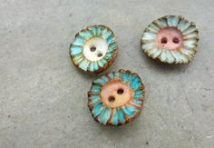 cloud flower buttons   3 wee ridge sculpted painted porcelain buttons that make me think of sunflowers and sky  these buttons measure approx 1.8cm - 0.7inches  do check your measurements and take a peek at the handheld picture for a sense of scale    I have found that porcelain suits these organic slender forms so well, it allows me to create intricate textures and very thin pieces that are strong and light. they have a lovely chinkchink music to them.  I hand shape, imprint and carve the…
