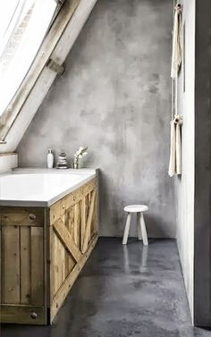 concrete bathroom with old wood clad tub