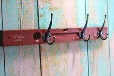 Rustic red carpenters level with unique stamping details has been repurposed into a hook rack. Three distressed, metal hooks are attached for