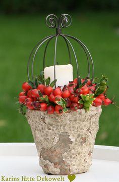 Wasserdichtes Gefäß mit Steckschwamm ausfüllen und mit Hagebutten dekorieren. Kerze andrahten und in der Mitte platzieren.