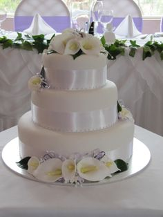 "round 3 tier white wedding cake with Calla Lillies - My first wedding cake for a formal wedding. 3 tiers, fruit 12"" chocolate 9"" and 6"" fruit for the bride to freeze. I made the  Calla lilies and filled  with white and lilac filler flowers and white and lilac fine ribbon."