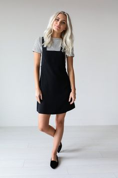 "• Trendy black overall dress. • Available in S, M, L. Model is 5' 7"" and wearing a size small • 100% Polyester"