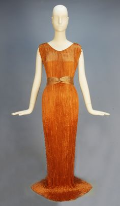 FORTUNY COPPER DELPHOS GOWN and STENCILED BELT, 1930s. Sleeveless pleated silk having fixed neckline, the side seams decorated with silk cord and striped Murano glass beads, twisted silk belt stenciled in silver ginko leaves, selvedge stamped Made in Italy Fabrique en Italie Fortuny depose. With orignal Elsie McNeill, Inc. square box. L-61 to 65 center back, Belt 2 x 27, can be adjusted.