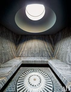 Book-matched marble lines the steam room, which is crowned by a circular skylight   archdigest.com