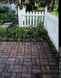 PATIOS/WALKWAYS: Basket weave pattern brick walk along white picket fence, flower border, flagstone stepping stones.