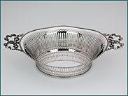 Hollands zilveren cakemand met strikhandgrepen  2e gehalte  Afmeting 28,7 (incl. grepen) x 17,1 x 6,6 cm  Gewicht 338 gram  Jaarletter M = 1922  Meesterteken Gebr. Seton - Schoonhoven