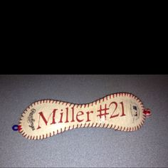 Cut a baseball, restitch with felt on back, attached a baseball bead and elastic. Cut the letters with Cricut using sticky back vinyl. Done!