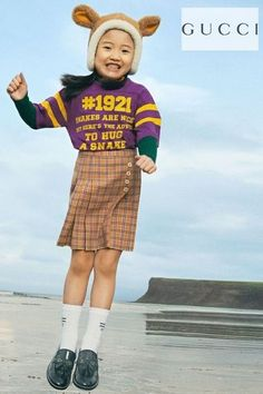 Gucci Girls Fall Mini Me Streetwear look. Purple oversized t-shirt with 1921 logo print & yellow stripes on the sleeves. 'To hug a snake' is printed in yellow on the front and 'l'aveugle par amour' 'blind for love' on back. Orange soft wool skirt in 1970s vintage purple check pattern and pleated styling. Complete the look with a pair of black patent leather shoes. Shop Gucci girls clothes @ Childrensalon (affiliate). #gucci #guccigirl #minime #girlskirt #childrensalon #dashinfashion Gucci Baby, Gucci Kids, Blue Ivy Carter, Girls Designer Clothes, Purple Snake, Girls Special Occasion Dresses, Black Patent Leather Shoes, Orange Skirt, Celebrity Kids