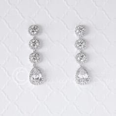 A single pave set pear cut CZ jewel hangs below three round, brilliant cut pave stones. These earrings are beautiful and will highlight your special occasion. AAA grade CZ, rhodium or rose gold plate,