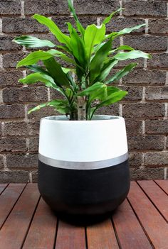 Hand-painted lightweight plant pot white and black with metallic silver stripe. This is a striking design which will add a touch a glamour to your home! The material of the pot is fibreglass and painted using water-based paint. Small - 25 x 25cm Medium - 35 x 35cm Large - 45 x 45cm  Our pots have their own personality and imperfections which is what makes them unique. As the pots are hand painted they are delicate and need to be handled with extra care. They are intended for indoor use or in…