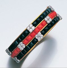 A coral, onyx and diamond bangle, by Kutchinsky, 1976  The 18 carat yellow gold hinged bangle, set to the front with alternate rows of sugarloaf onyx and coral in channel settings, accented at intervals with applied brilliant-cut diamond quatrefoil clusters, signed Kutchinsky, London hallmarks for 1976, diamonds approximately 3.20 carats total, inner diameter 5.6cm.