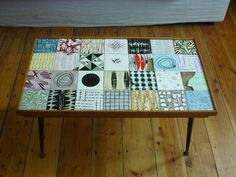 This could be a DIY project. tiles in collage form in a wood frame...add table legs.