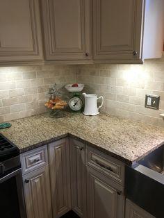 New Traventine back splash, Giallo Ornamental granite complement White Mushroom cabinets.