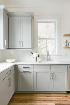 A single window in a transitional kitchen surrounds dove gray shaker cabinets with floating wood shelves.