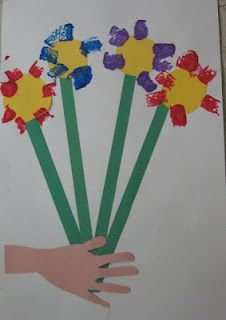"""based on Pablo Picasso's """"Hand With Flowers."""" The children trace their hands onto skin colored construction paper and glue onto white paper. Then they make stems from green construction paper. They sponge paint their flowers above the stems."""