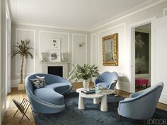In the drawing room of Colin Radcliffe's Notting Hill home, a 1950s sofa and chairs by Ico Parisi, all covered in a Bruno Triplet velvet, surround a cocktail table by Angelo Mangiarotti, the 18th-century gilt-wood mirror is Italian, and the 1970s magazine rack is by Maison Jansen; the prints above the fireplace are by Victor Pasmore, the palm sculpture is by C. Jeré, and the walls are painted in Dulux's Grey Steel 2. Tour the rest of the home   - ELLEDecor.com