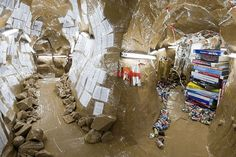 Thomas Hirschhorn Cavemanman, 2002 Wood, cardboard, packing tape, aluminum foil, books, posters, videos, mannequins, cans, shelves, spray paint, and fluorescent light fixtures Reference for cafe/Paris environment, particularly the packing tape rocks!