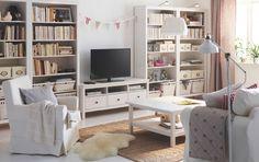 Salón luminoso con un mueble de TV de pino macizo tintado en blanco con cajones, cuatro estanterías con cajas y libros, una mesa de centro blanca, un sofá de dos plazas con chaise longue y un sillón blanco.