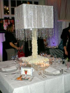 A lampshade for a wedding centerpiece. Crystals drape down the sides of the shade and the base is made of white compacted carnations