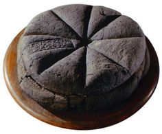 A loaf of bread made in the first century AD, which was discovered at Pompeii, preserved for centuries in the volcanic ashes of Mount Vesuvius. The markings visible on the top are made from a Roman bread stamp, which bakeries were required to use in order to mark the source of the loaves, and to prevent fraud.