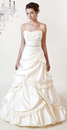 A strapless gown with unique accordion pleats, with beaded belt at natural waist.