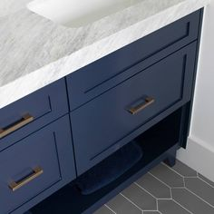 Fresh navy cabinets for this teenage boy's bathroom with modern gray tile and organic granite. Livable luxury at its best!