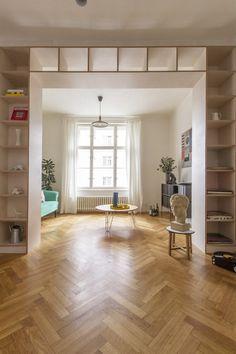 Hlavní obytný prostor rozděluje na tři části velká knihovna. Parkety dodávají bytu luxusní nádech.