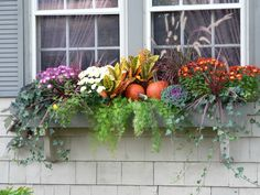 A couple pumpkins and some colorful kale transforms the window box into a celebration of autumn.