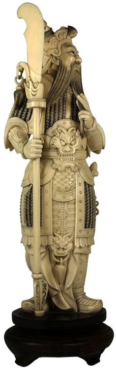 Ivory Carved Figure of Guan Yu holding a broadsword & stoking his beard. Standing on a carved timber silver inlaid stand. With some restoration to the blade. Height not including stand - 32cm