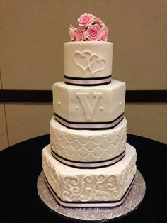 Pink and black accent wedding cake with round and hexagon tiers