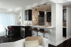 In this small New York City apartment, opening the kitchen wall allowed the kitchen design to spill into the living area, offering additional storage, seating and a bar. Matching black cabinetry ties the bar and kitchen together, and crisp white walls keep the space feeling bright and clean.