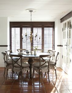 Casual Shutters  Install wood shutters in a dining room instead of drapery to keep the room relaxed.  Wood shutters are a staple for casual, seaside style. When open, they invite plenty of sunshine; closed, they keep interiors cool. Shiny terracotta floor tiles add Mediterranean warmth, while a raw-wood pedestal table and X-back chairs slip-covered in linen add to the cottage theme.