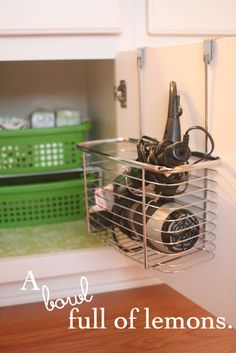 basket on the inside of bathroom cabinet door for blow dryer, etc