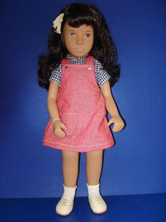 """Sasha Brunette """"Red Pinafore"""" #111 is an appealing faced jointed vinyl Sasha doll that was manufactured in England by Frido/Trendon/Sasha Dolls Ltd. circa 1980-86. She still wears her silver Sasha Serie medallion with script on both sides. 