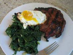 ... delmonico steak with garlic wilted greens topped with a pan fried egg