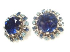 Large Blue rhinestones are the center piece on this pair. They are surrounded by smaller dark and powder blue stones in a silver setting.