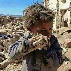 A Syrian boy stands in the rubble of his city. He has likely lost his home. He looks like he's lucky to have survived whatever has happened.