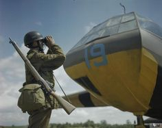 A paratrooper looking through binoculars with his rifle over his shoulder while sheltering under the nose of an Airspeed Horsa Glider of No 21 Heavy Glider Conversion Unit. The paratroopers were taking part in a Press Facility Day exercise 24th June 1943