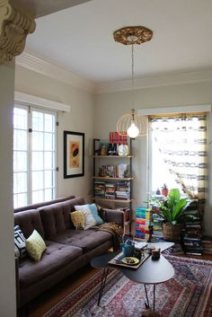 Persian style rug + industrial light fixture + neutral coach + yellow pillows + book stacks