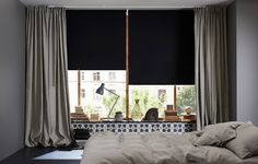 A bedroom featuring large windows with black block-out roller blinds and one layer of thick gray curtains for cozyness and silence.