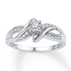 Ribbons of diamond-studded sterling silver curve around a lovely center diamond in this gorgeous promise ring for her. The ring has a total diamond weight of 1/8 carat. Diamond Total Carat Weight may range from .085 - .11 carats.