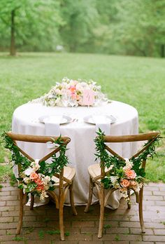 Brides.com: . Crossback chairs are upgraded with hanging floral garlands at this outdoor sweetheart table.