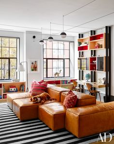 A Living Divani sectional sofa is paired with a custom-made John Robshaw rug in the playroom; the ceiling lights are by Michael Anastassiades for Flos, the floor lamp is by Ralph Lauren Home, and the Norman Cherner chairs at the desk unit are by Design Within Reach.