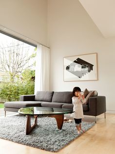 The living room is outfitted with the Stockholm Wool Rug from Ikea, a Noguchi table by Isamu Noguchi for Herman Miller, and the Neo Sectional Chaise Left by Niels Bendtsen from DWR.