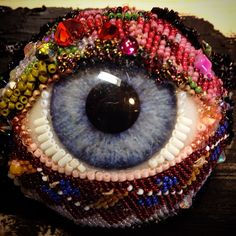 Eye Candy.....I couldn't figure out how to integrate the compression of beads with the open space of this large eye (2 plus inches across), and then I started glueing beads onto the eye itself. Problem solved for now. www.byart.com Betsy Youngquist
