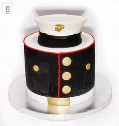 A Cake for a Marine - 8 inch round dark chocolate cake with strawberry compote and dark chocolate ganache. Covered in black and white fondant with fondant accents, meant to replicate dress blue blouse. Cover made from gum paste, gold accents painted with gold dust and vodka.